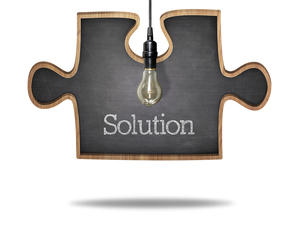 Solution concept on puzzle shape black blackboard with light bulb hanging